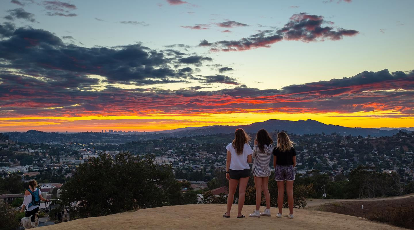 Students standing on Fiji Hill at sunset