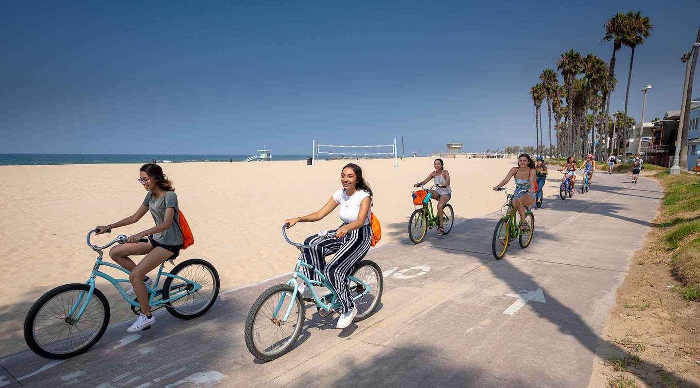 Students biking near the ocean in Venice