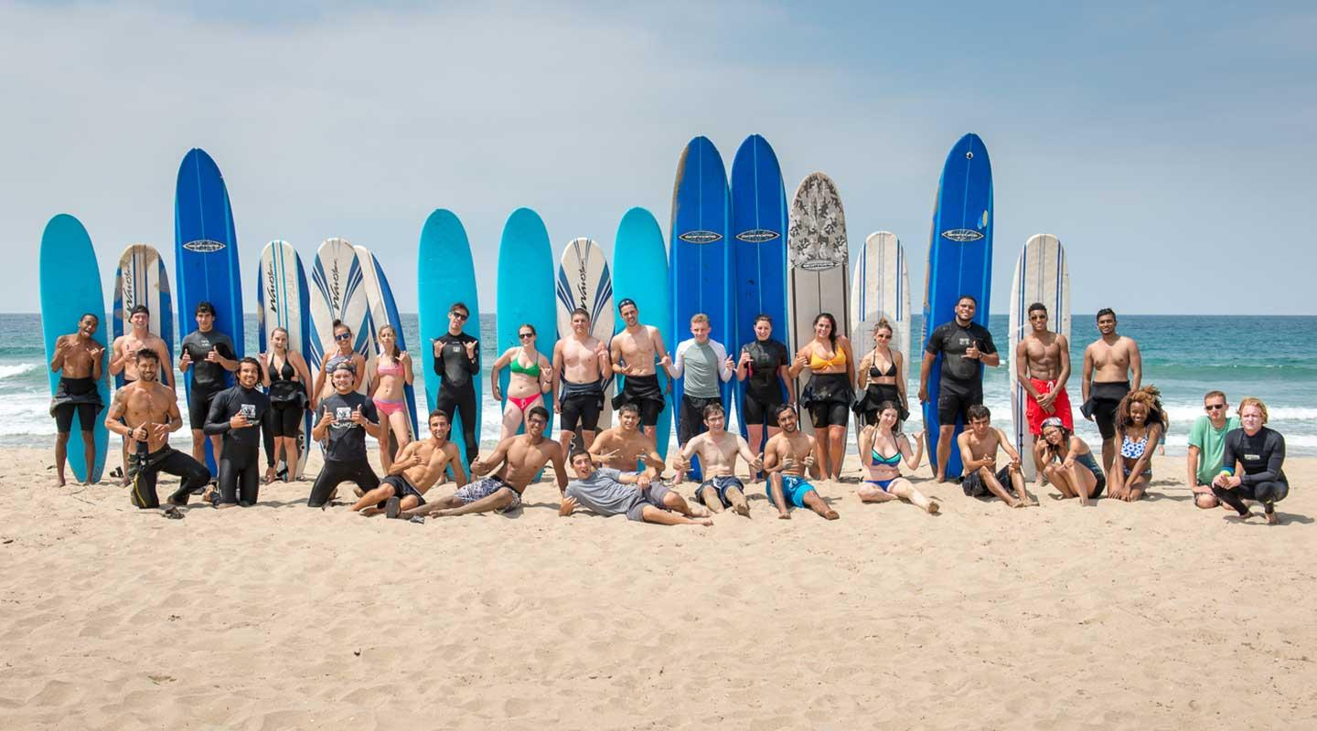 Oxy students posing with surfboards by the beach
