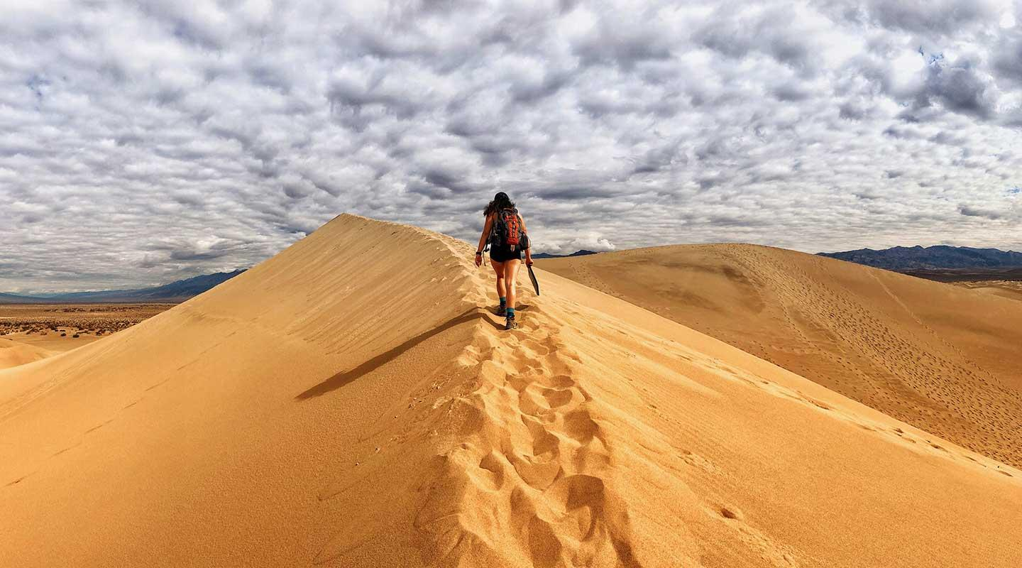 A student hiking along a sandy ridge in the desert with dramatic sky