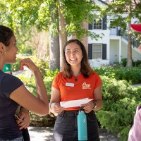 Smiling tour guide wearing orange shirt with Oxy logo, backed by Collins House