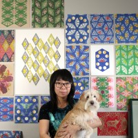 Jennifer Zee carrying her dog in front of art