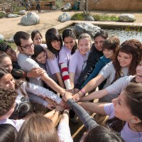 Oxy students in a huddle amid community service work