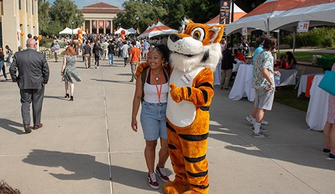 Campus visitor smiles and poses for a photo with Oswald, Oxy's mascot, in front of full view of Thorne Hall and visitors