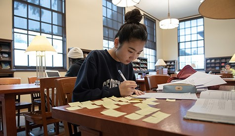 A student studies with sticky notes and books in the Academic Commons