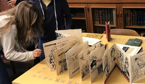 Students examine an old printed brochure from Oxy's special collection
