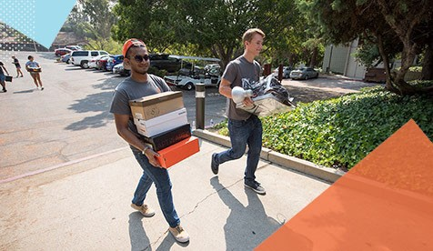 students carrying boxes on campus