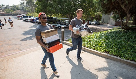 Two students carry boxes as they move into their residence hall