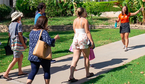 Student tour guide in orange T shirt leads visitors through green spaces at Oxy along a sidewalk