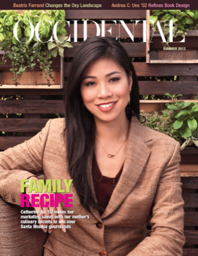 A woman in a brown suit jacket sits smiling on a bench. Cover story: Family Recipe