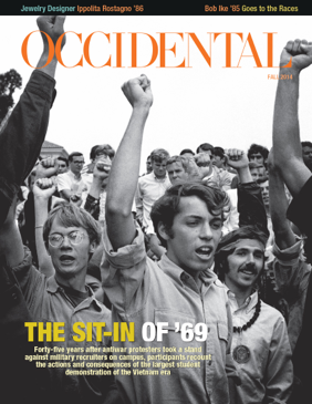 A black and white photo of a crowd with their fists raised. Cover story: The Sit-In of '69