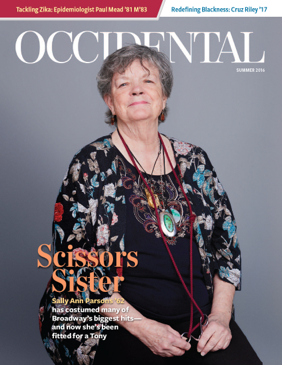 A woman in a colorful shirt sits before a grey background. Cover story: Scissors Sister