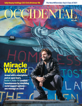 A man crouches in front of a mural of the Statue of Liberty. Cover story: Miracle Worker.