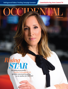 A woman in a white shirt stands confidently with her arms crossed. Cover story: Rising Star