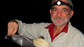 Dr. Rodrigo A. Medellín holding a bat