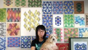 Jennifer Zee holding dog in front of art