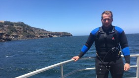 Ryan Freedman on boat with diving gear