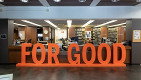 """Large wooden orange sign reading """"FOR GOOD"""" rests in front of a library circulation desk."""
