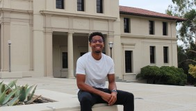 Micah Wilson '22 seated on bench outside of large academic building.