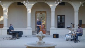 A jazz trio of piano, bass, and drums performing in the Booth Hall courtyard