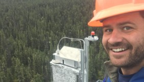 Troy Magney above trees with hard hat and equipment