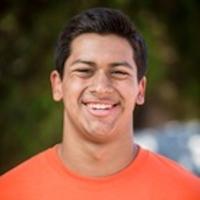 Dominic Rios, a young man, smiles at the camera.